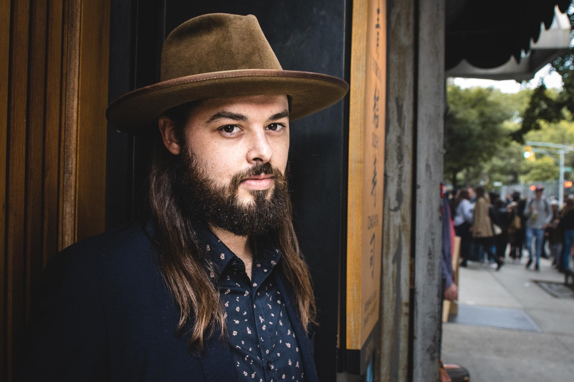 The cover for Caleb Caudle's album titled 'Better Hurry Up' depicting the artist seated in a chair while wearing a hat and sunglasses.