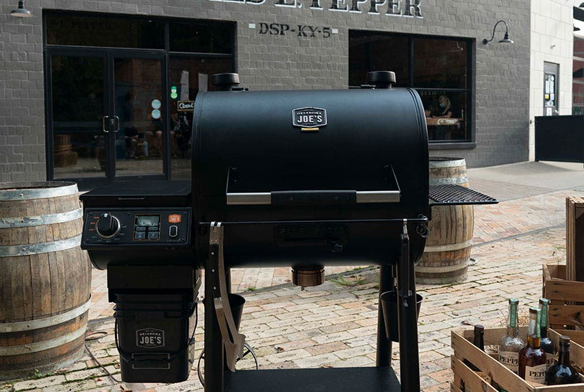 Scenic photograph of the Oklahoma Joe's® Rider DLX Pellet Grill surrounded by rustic barrels and wooden crates.