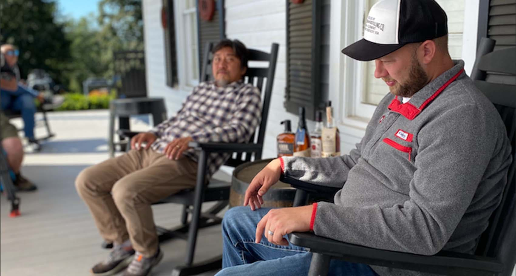 Chef Edward Lee and Freddie Noe Jr., 8th generation family distiller at Jim Beam, sitting on a porch with bourbon on barrel