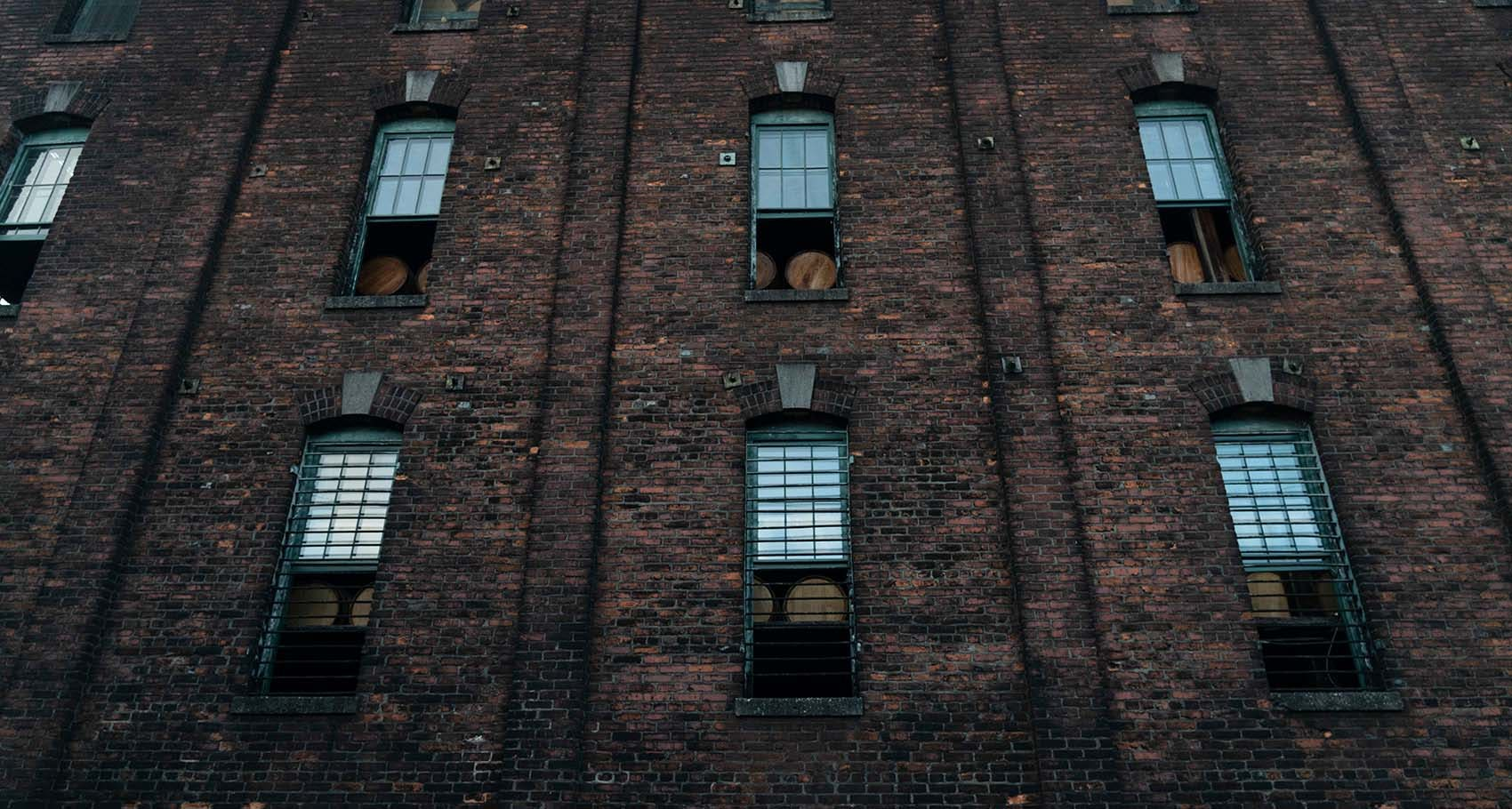 Buffalo Trace Distillery view of outside brick building with bourbon aging in barrels in windows